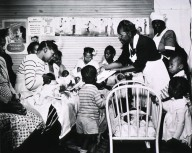 Maude Collen, an African American nurse midwife, offers instruction to new mothers in a nursery.
