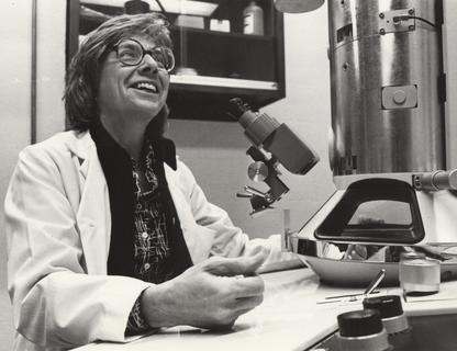 Ruth Bleier sitting at her electron microscope, 1980's