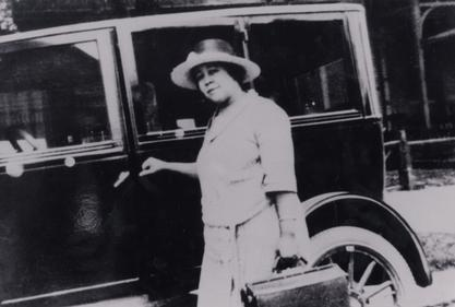 Justina Carter Ford on a house call in front of her car, 1920s