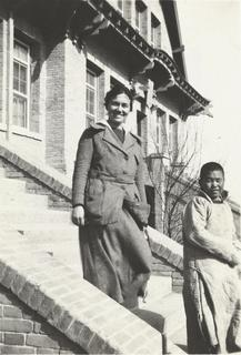 Lois Pendleton Todd with a patient on the steps of the Williams-Porter Hospital in Tehchow, Shantung, China, 1920s
