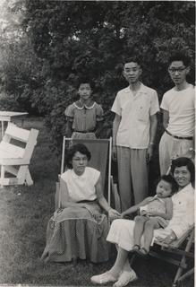 Rebekah Wang-Cheng sitting on her mother's lap along with other family members Ruthie, Ester, John, and her father, ca.1956